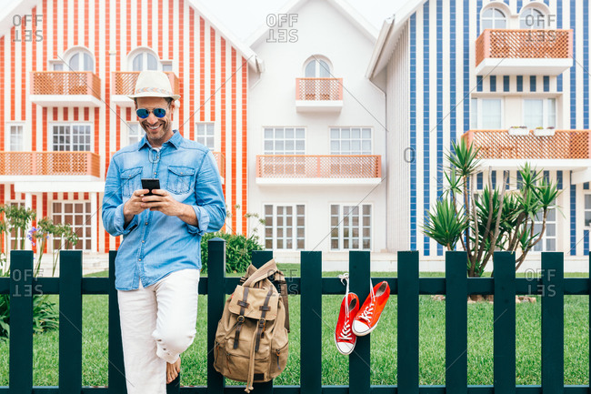 Full body smiling trendy man with backpack standing on sidewalk of Costa Nova with sneakers on fence and using phone