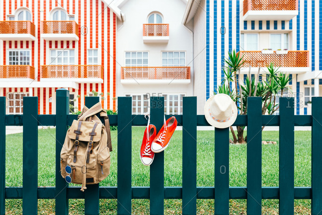Colorful red sneakers of traveler with hat and backpack hanging on fence against striped houses of Costa Nova