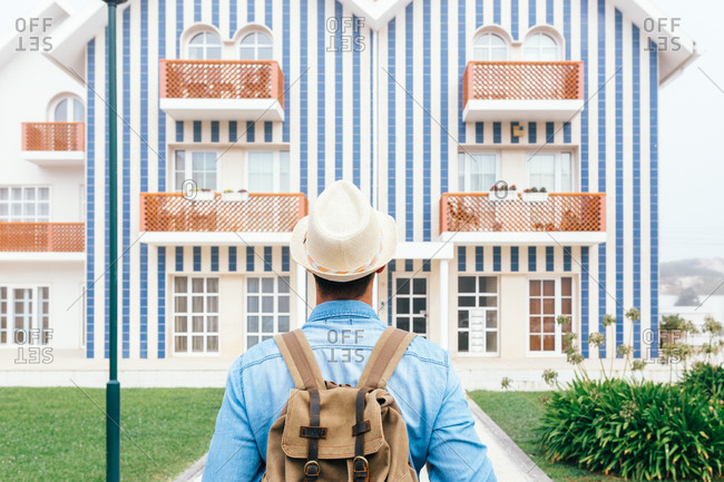 Back view of man with backpack standing at fence on Costa Nova and looking at colorful striped houses