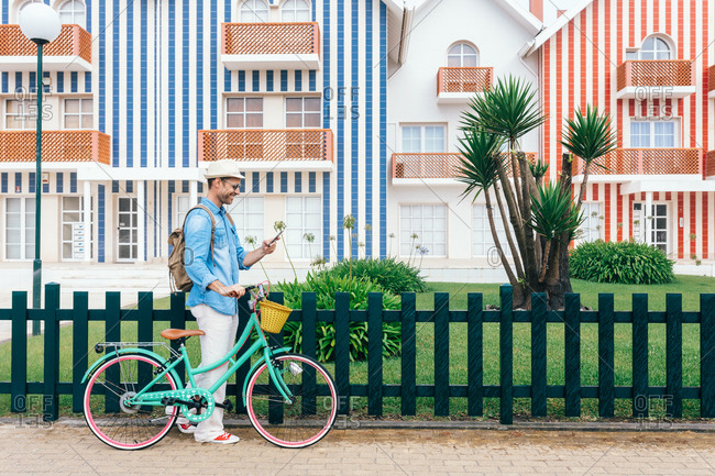 Trendy adult man browsing smartphone and walking with vintage bicycle against Costa Nova houses