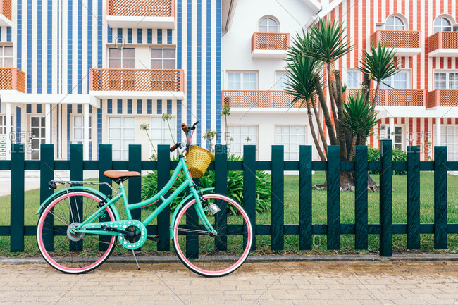 Parked vintage bicycle with basket at fence on sidewalk with striped buildings on Costa Nova do Prado in Aveiro