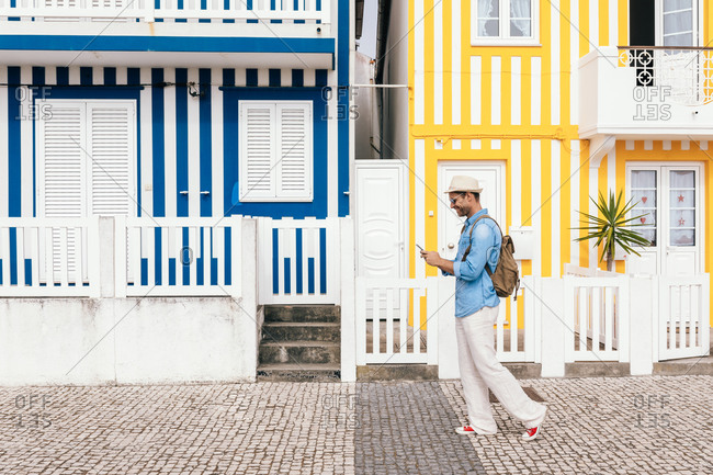 Side view of stylish man in hat using smartphone against creative facades of Costa Nova buildings