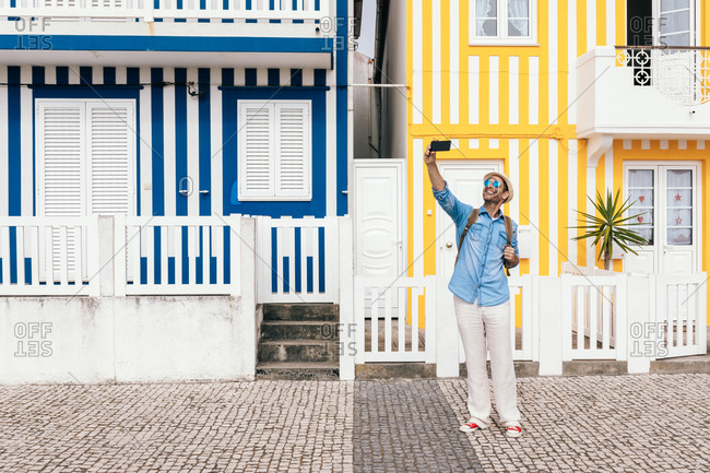 Trendy hipster tourist in hat and sunglasses using smartphone to take selfie against striped colorful house of Costa Nova in Aveiro