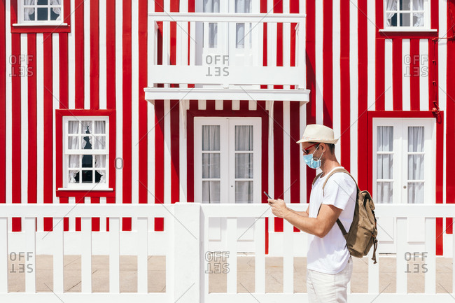 Side view of hipster tourist in medical mask using smartphone standing against striped house on Costa Nova