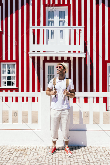 Full body happy guy in white outfit standing with backpack against colorful striped house on Costa Nova