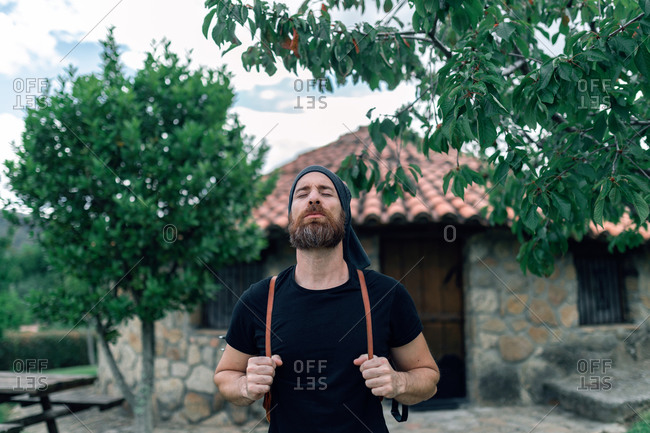 Calm male tourist with backpack standing near stone house in settlement