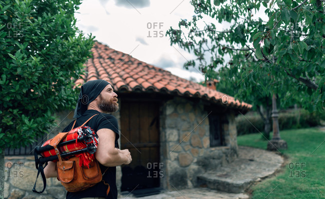 Back view of calm male tourist with backpack standing near stone house in settlement and looking away