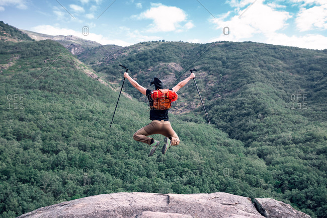Back view of faceless male hiker with trekking poles and backpack in moment of jumping with outstretched arms on background of mountainous landscape