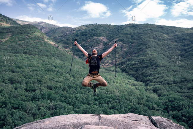 Hiker with trekking poles and backpack in moment of jumping with outstretched arms on background of mountainous landscape