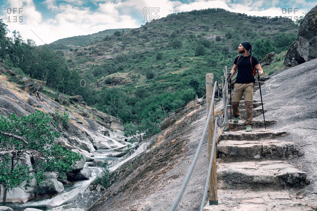 Tranquil traveling man with trekking poles walking down stone stairs and admiring majestic scenery of highlands during holiday
