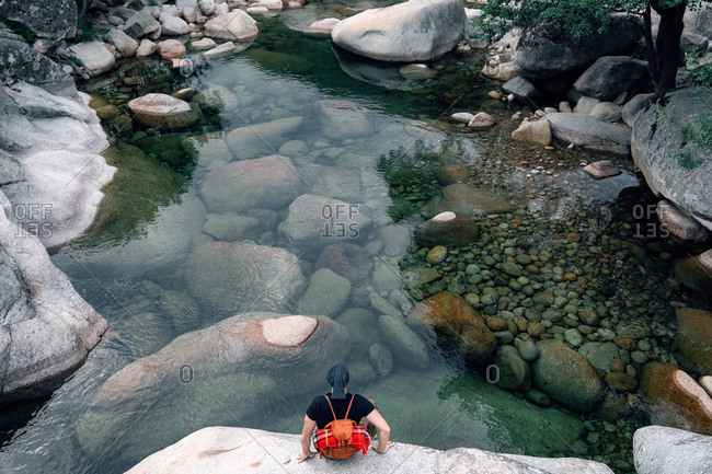 From above of anonymous male traveler with backpack sitting on rock and enjoying picturesque view of river in highland area
