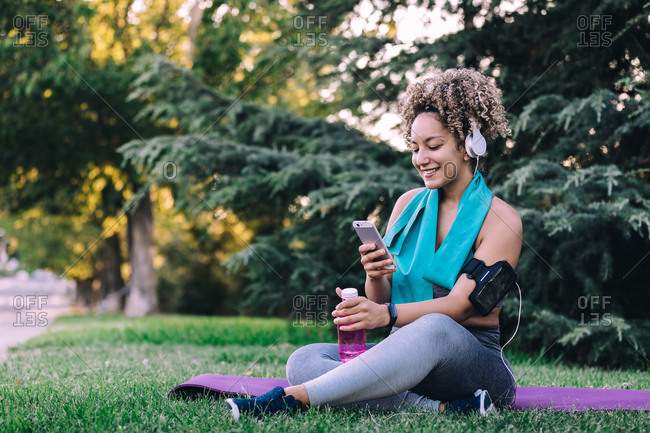 Full body cheerful young curly haired female in sportswear with headphones sitting on grass and browsing smartphone while resting with bottle of water after workout in summer park