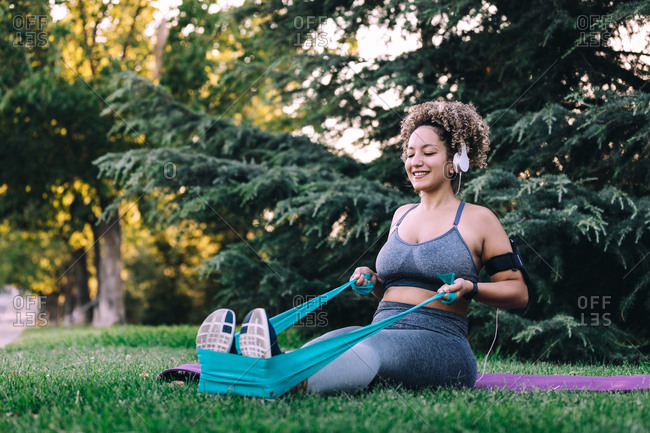 Full length cheerful young female in activewear with headphones sitting on green lawn and doing exercise with elastic band during fitness workout in park