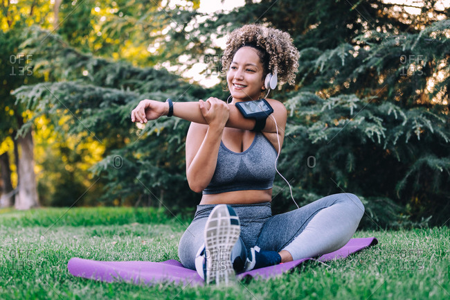 Full length positive young ethnic female with Afro hairstyle in sportswear stretching arms and shoulders and listening to music with headphones and smartphone while training on green lawn in park