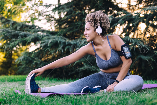 Happy young ethnic female with curly hair in sportswear listening to music with headphones and smartphone and doing seated forward bend exercise while stretching body during fitness training in summer park