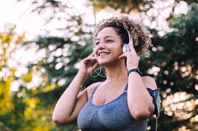 Low angle of optimistic young ethnic female with Afro hairstyle adjusting headphones while listening to music on smartphone during training in green park