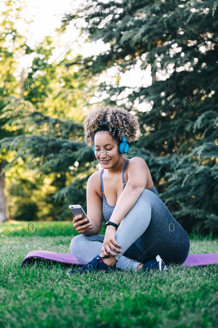 Full body cheerful young curly haired female in sportswear with headphones sitting on grass and browsing smartphone while resting after workout in summer park