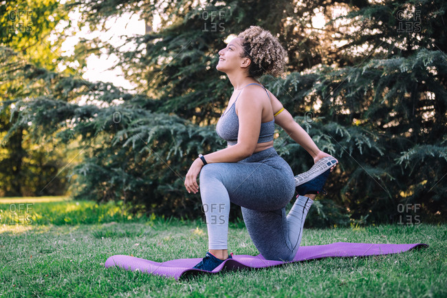 Full body side view of positive ethnic sportswoman doing lunge on knee exercise while stretching legs during workout on green lawn in park