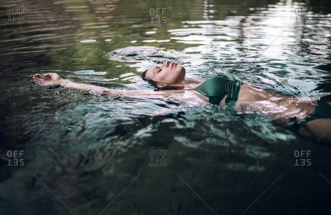 Relaxed female in bikini lying on water of pond and enjoying summer vacation with closed eyes