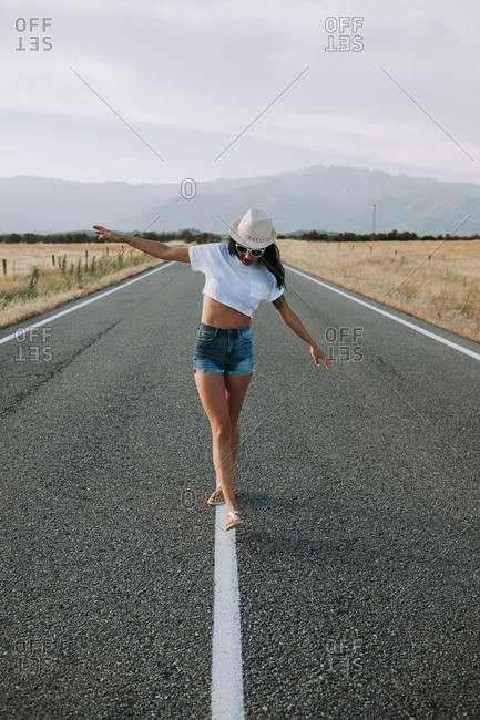 Serene female traveler in summer wear walking with outstretched arms along empty asphalt roadway on background of mountainous landscape and enjoying freedom