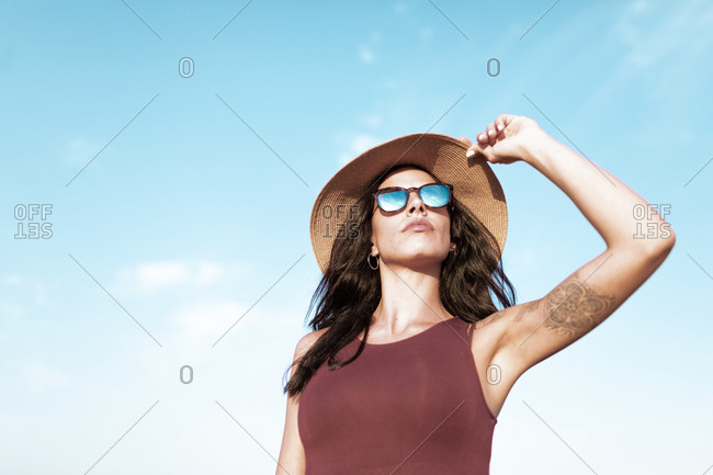 Carefree female traveler in summer dress and sunhat walking along empty roadway and looking away while enjoying freedom