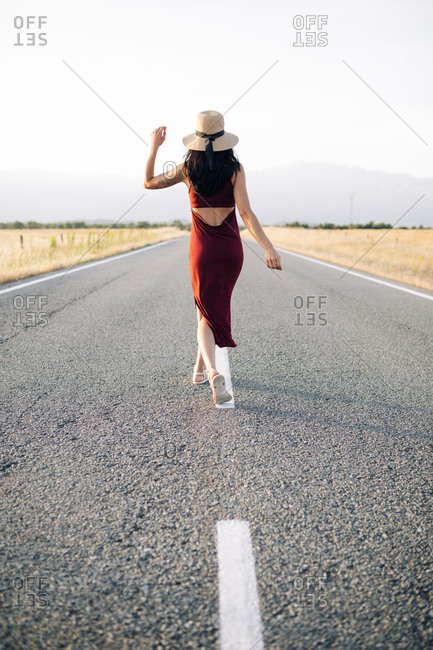 Back view traveler in summer dress and sunhat walking along empty roadway and looking away while enjoying freedom