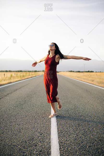 Carefree female traveler in summer dress walking along empty roadway with outstretched arms and looking away while enjoying freedom