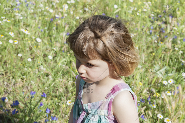 Side view of cute kid standing on grass and making funny faces while enjoying weekend in summer