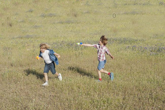 Positive brothers in summer wear running in meadow and playing with water guns while entertaining during weekend in countryside