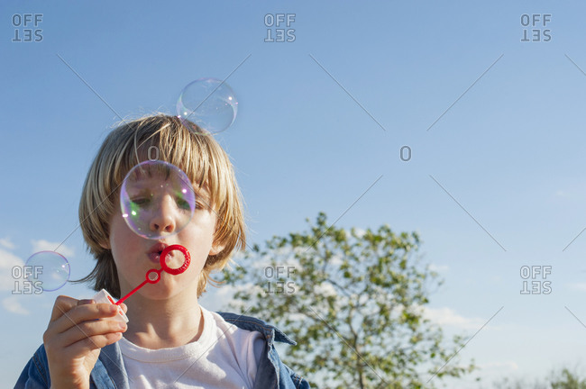 Cute child standing in park and blowing soap bubbles while entertaining during summer weekend