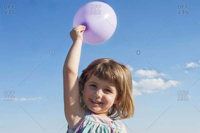 Smiling little child in summer dress standing with balloon in raised hand on background of blue sky and looking at camera