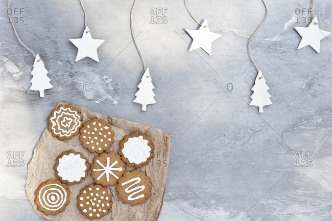 Plate with assorted gingerbread cookies with white icing placed near gray wall decorated with craft star and tree shaped paper items