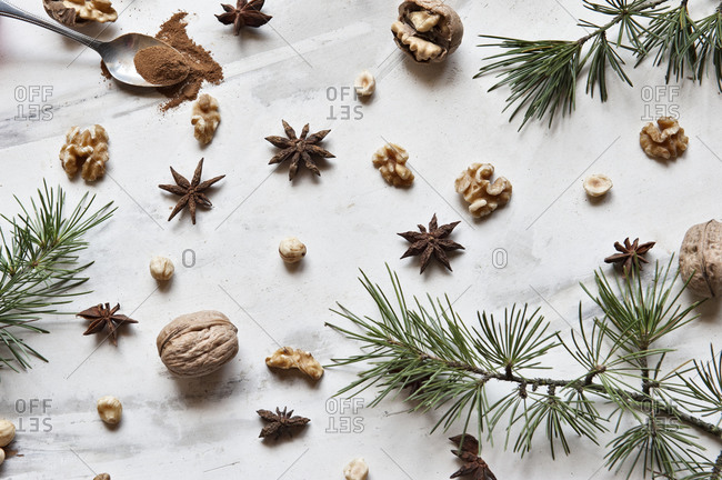 Xmas decoration including natural green fir branches composed with walnuts and aromatic anise stars on white marble surface