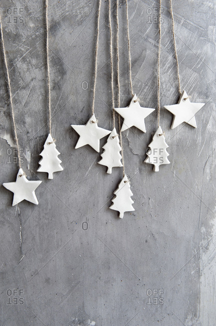 Creative Christmas background with white craft stars and fir trees hanging on shabby gray surface