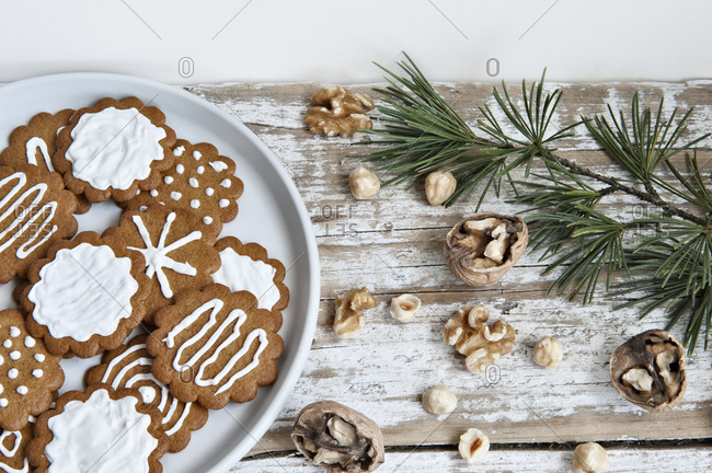 Top view composition with sweet homemade Christmas cookies decorated with white sugar icing served on plate placed on wooden table near various nuts and fir branch