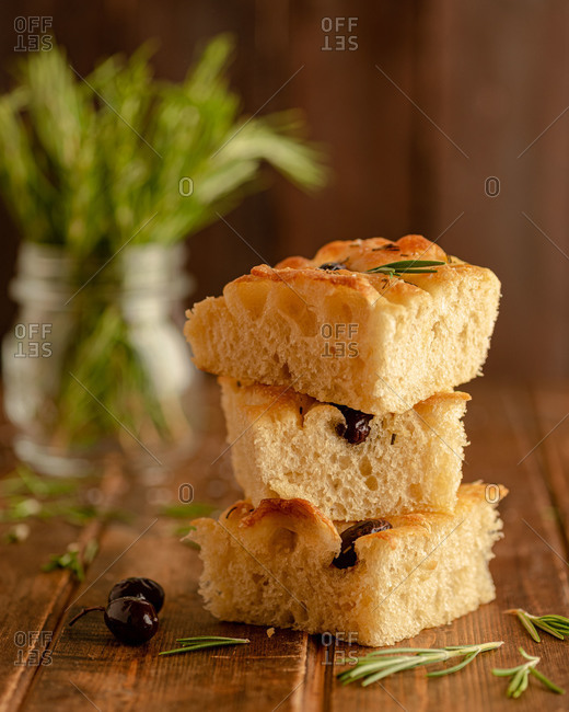 Pieces of freshly baked aromatic focaccia bread with black olives and fresh rosemary served on wooden tray