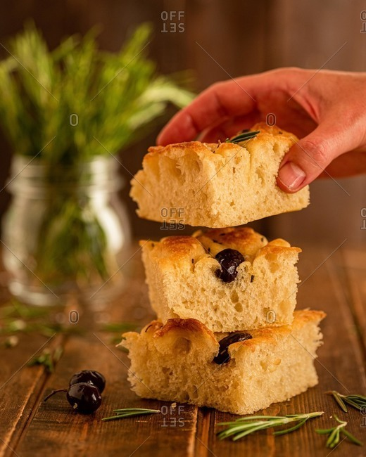 Crop anonymous person taking piece of fresh homemade focaccia bread with olives and rosemary from wooden table