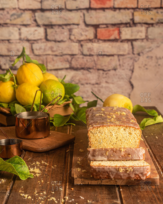 Delectable homemade whole lemon and poppy seeds cake garnished with sugar glaze and lemon zest served on wooden board on table with ingredients