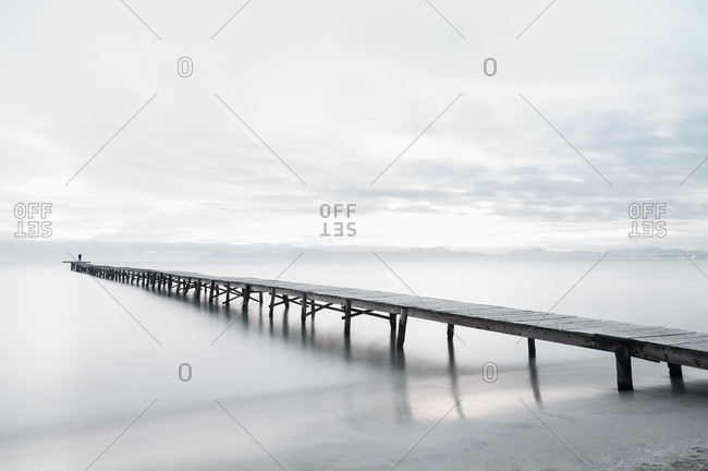 Peaceful scenery of sea with long wooden quay during foggy morning in Playa de Alcudia in long exposure