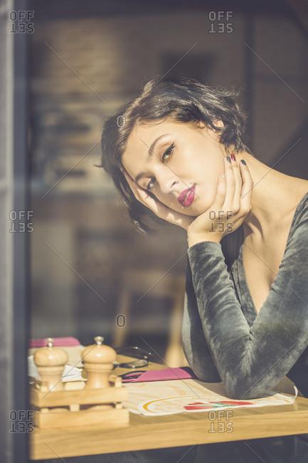 Beautiful woman sitting by window inside a restaurant