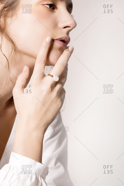 Pretty woman posing in the studio in white shirt and gold ring