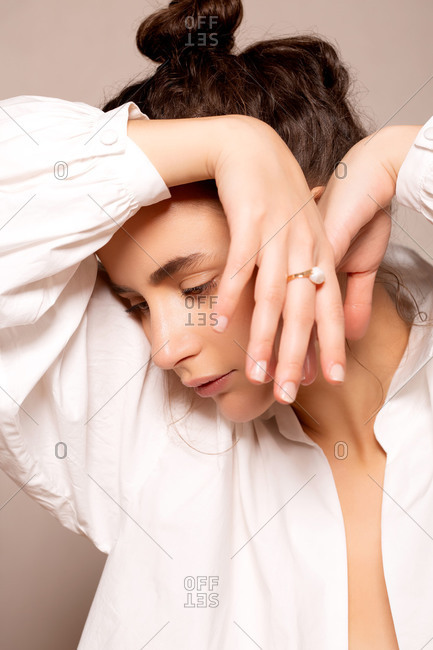 Attractive woman wearing a white shirt with her arms draped over her head