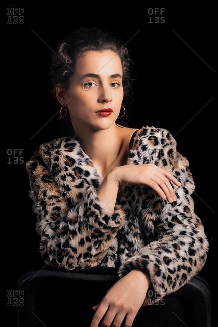 Woman posing in studio wearing a furry animal print jacket