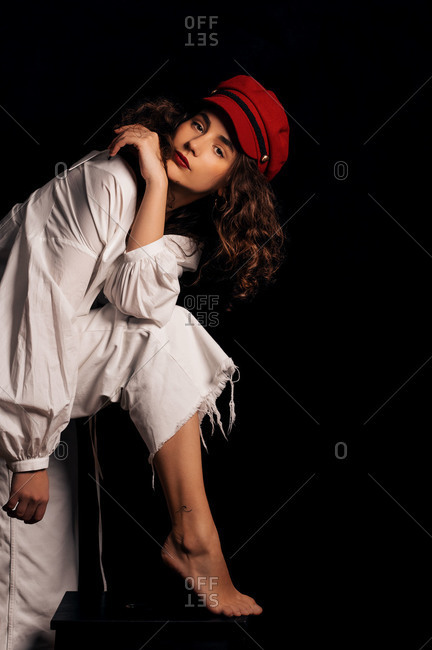 Seductive woman posing in front of black background wearing a red newsboy hat