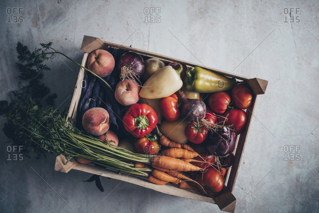 Fresh vegetables in crate on gray concrete surface