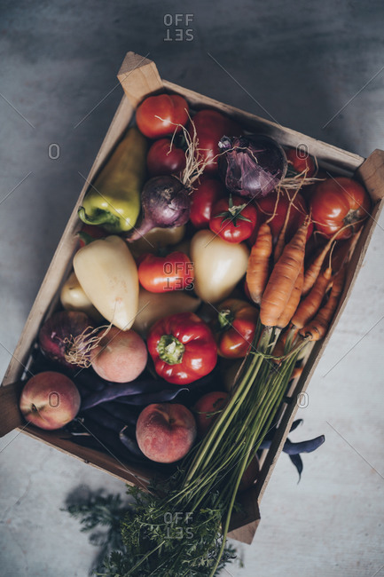 Variety of fresh vegetables in crate on gray concrete surface