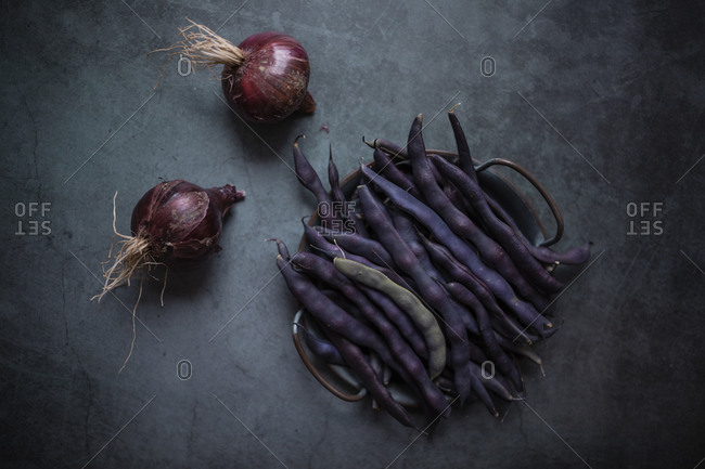 Purple pea pods and red onions on a dark gray concrete surface