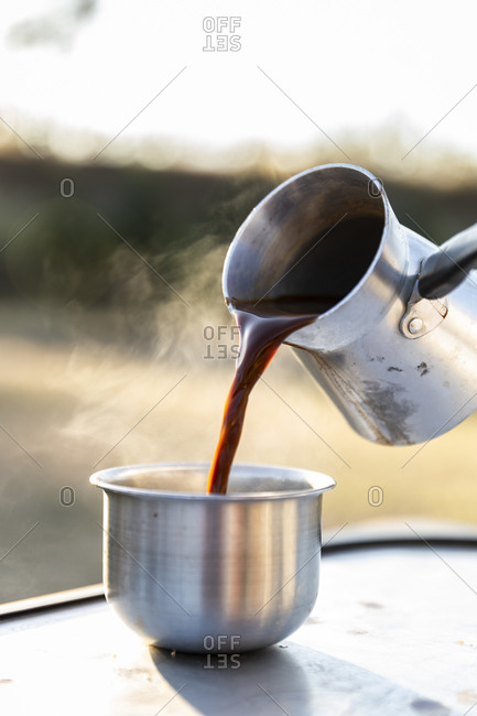 Turkish coffee being poured into a metal camping dish