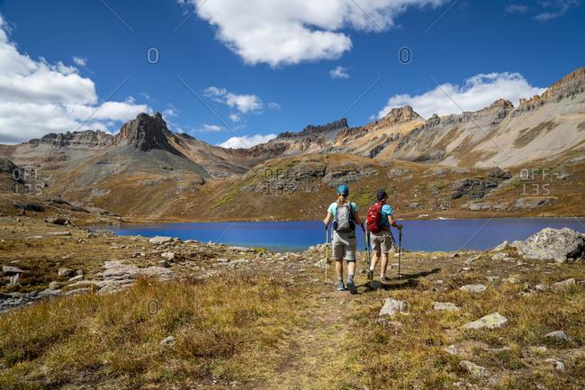 USA, Colorado, San Juan Mountains - October 8, 2017: Two hikers near Blue Lake, San Juan Mountains, Colorado, USA