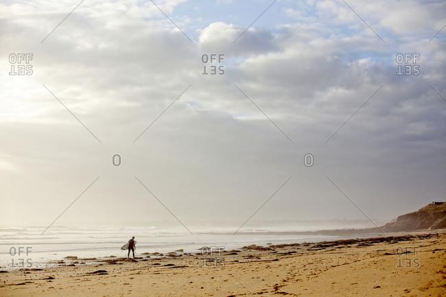 France, Morbihan, Le Loch - March 30, 2017: Surfer on beach, Leach Loch Guidel, Brittany, France
